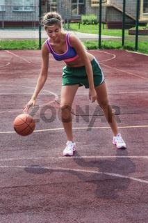 woman in sportswear with basketball ball