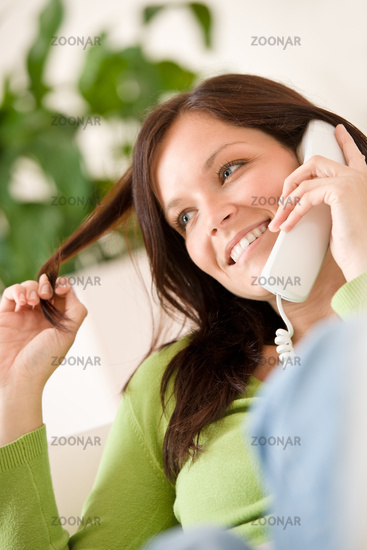 On the phone home: Happy woman calling