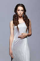 Beauty portrait of young woman in nightie. Brunette girl with long hair plaits and day female makeup on gray background
