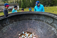 Visitors looking at bills lying in the giant bronze cauldron of the Manzushir Monastery, Mongolia