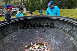 Besucher schauen auf Geldnoten im riesigen bronzener Kochkessel, Manzushir Kloster, Mongolei