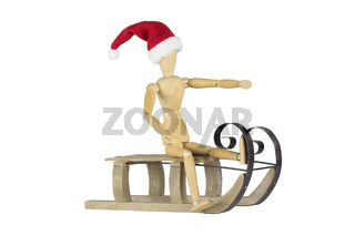 Wooden mannequin on a sleigh wearing a santa hat