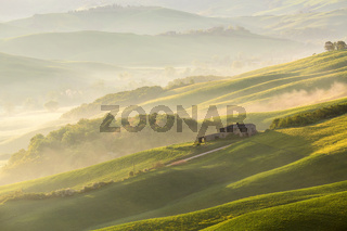 Italian Farmhouse in the valley with fog at sunrise