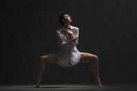 Sexy brunette dancing gracefully in the dark shot