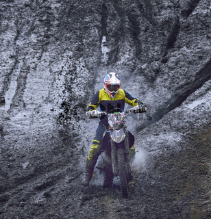 motorcyclist overcomes the obstacle of mud