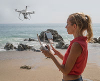 Pretty woman taking photos with drone camera