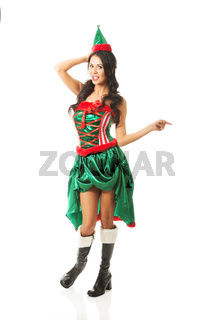 Full length woman wearing elf clothes pointing to the right