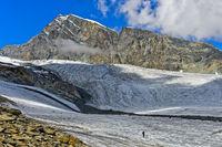 Hiker crossing the glacier Allalingletscher, Saas-Fee, Valais, Switzerland