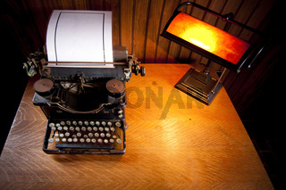 Desk with old typewriter and lamp
