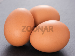 three eggs on slate background