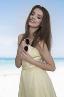 Young and happy woman in yellow dress posing with a sunglasses in the hand on the beach. Feeling free and joyful