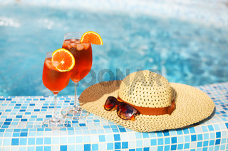 Glasses of orange alcohol cocktail on turquiose water background