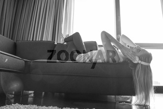 Lovely Blond Woman Listening To Music while resting on couch