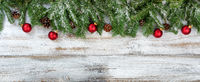 Christmas branches and ornaments on rustic white wooden background