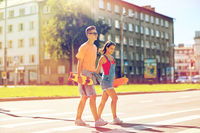 teenage couple with skateboards on city street