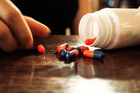 Orange-blue pills spilled out of bottle on polished wooden table and girls hand holding one of it