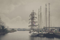 Three old sailing ships at the pier in the city harbor.