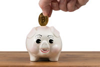 Gold coin being inserted into piggy bank