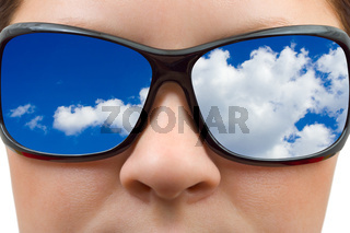 Woman in sunglasses and sky reflection
