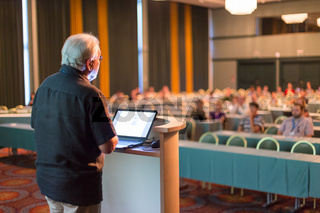 Senior public speaker giving talk at scientific conference.