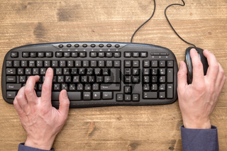 Businessman hand typing on keyboard with mouse