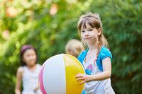 Mädchen und Freunde spielen mit einem Ball