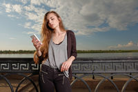 Pretty Young Woman Leaning Back Against Railings on Embankment While Using her Smartphone Reading Sms.