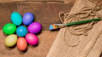 Pattern of painted eggs on wooden table for Easter with paintbrush