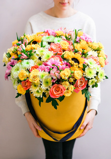 Luxury bouquets of mixed flowers in the hat box. roses in the hands women.
