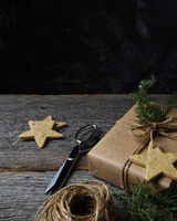A plain paper wrapped Christmas present on a rustic wood table with holiday cookies, twine, scissors