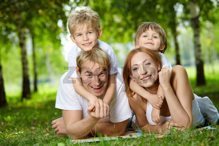 Happy family with two sons frolic on a lawn