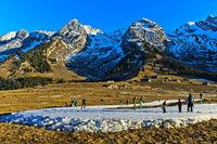Skilangläufer auf improvisierten Loipen aus Kunstschnee im schneearmen Winter