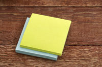 blank sticky note against wood