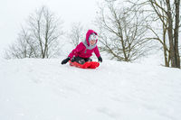 Girl with sleds outdoors on winter day