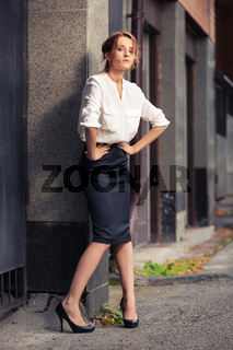 Young fashion business woman standing at office building