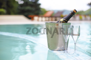 Ice bucket champagne bottle and two glasses near pool
