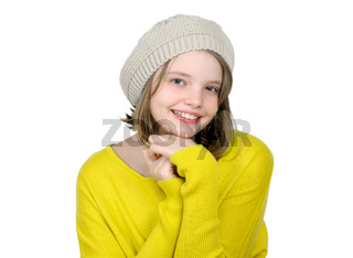 Portrait of a cute teen girl in a yellow sweater and a knitted cap.