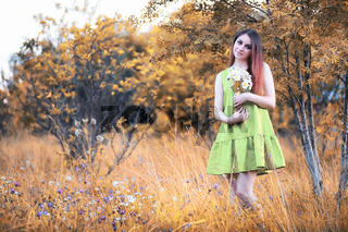 beautiful girl with a bouquet in autumn