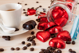 Red chocolate hearts in a glass jar and an espresso coffee