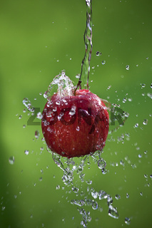 Apple with a splash on green background