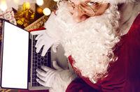 Santa Claus working on modern laptop