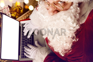 Santa Claus working on modern laptop