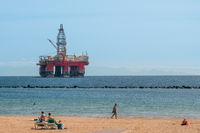 people on beach with drilling platform in background