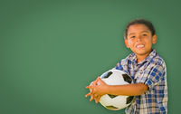 Cute Young Mixed Race Boy Holding Soccer Ball In Front of Blank Chalk Board