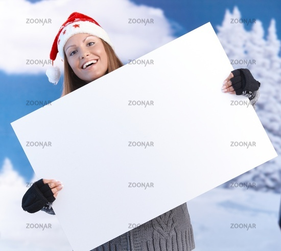 Happy girl in santa hat holding huge letter