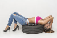 Young sexy woman with car tires