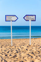 Two signposts standing on sandy beach