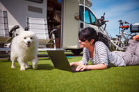 Woman on the grass with a dog looking at a laptop