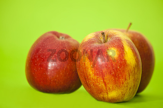 three red juicy apples on green background