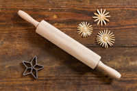 Rolling pin and baking pan and stars on weathered wooden board